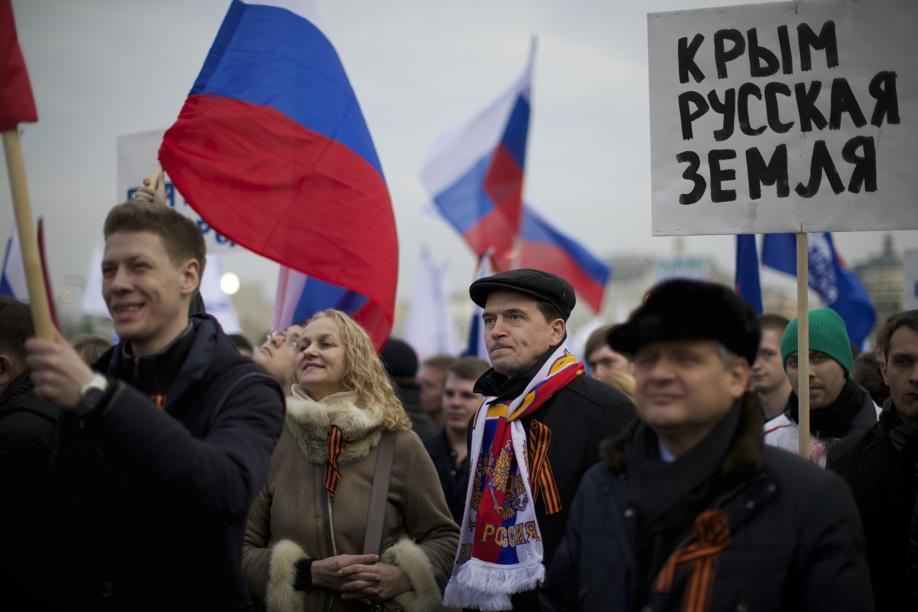 "Pro-Putin demonstrators held Russian national flags and posters reading ""Crimea is Russian land!"" in Moscow."